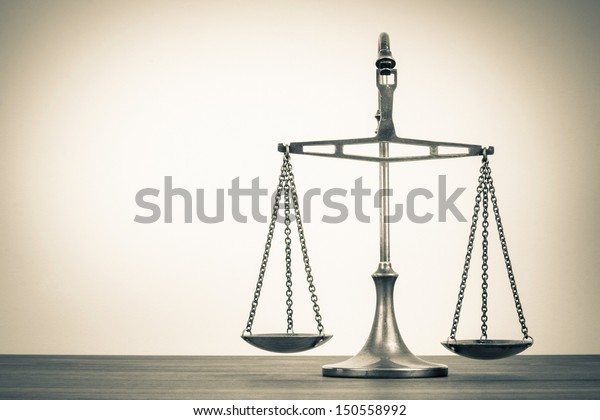 Law scales on table. Symbol of justice. Vintage sepia photo