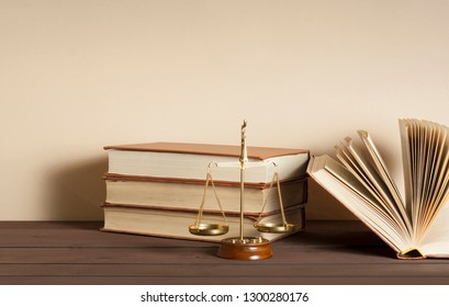 Law scales and stack of books on table in a courtroom.Concept of justice and law.
