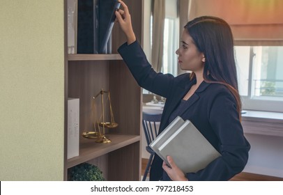 Law student trainee searching for Law books In the library at law office