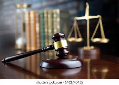 Law symbols in composition. Judge's gavel on wooden table. Library background.