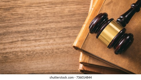 Law theme, lawyer's desk. Judge gavel on legal books, wooden background, copy space, top view
