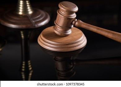 Law theme, mallet of judge, wooden gavel, mirror reflection background