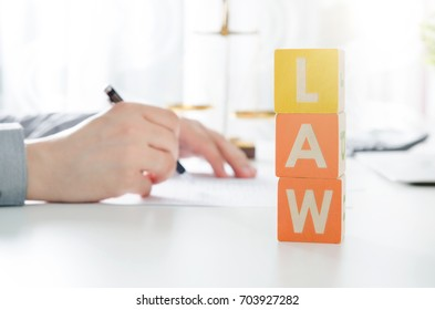 LAW word from toy blocks. Lawyer working in background. lawyer law justice judge scales courtroom blocks toy concept