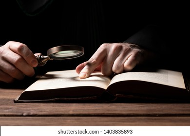 Lawer holding magnifying glass over  legal code. Criminal case investgation.