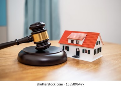 Lawn auction hammer and small house on the table, real estate mortgage auction