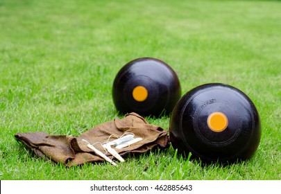 Lawn Bowls. Two wooden bowling balls on freshly cut grass with measuring device and leather cloth.