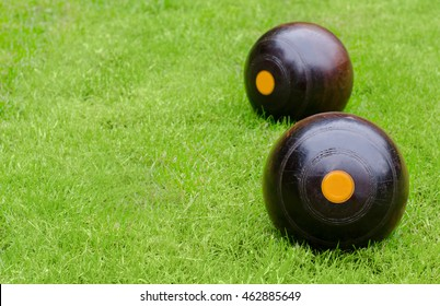 Lawn Bowls. Two wooden bowling balls on freshly cut grass with copy space.