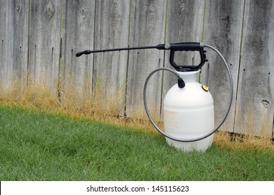 lawn chemical sprayer in front of fence