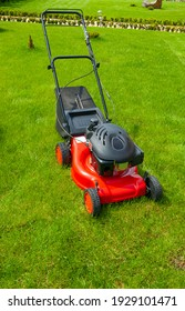 Lawn mover on green grass in sunny day.