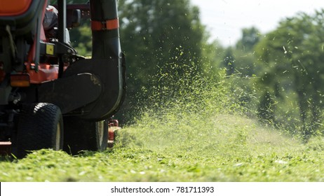 lawn mover at work on a green meadow at summertime