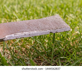 lawn mower blade that is rusty, damaged, and dull needing sharpened