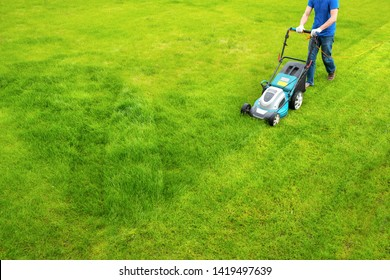 A lawn mower is cutting green grass, the gardener with a lawn mower is working in the backyard, a side view.