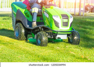 Lawn mower with driver mowing the grass on a green meadow