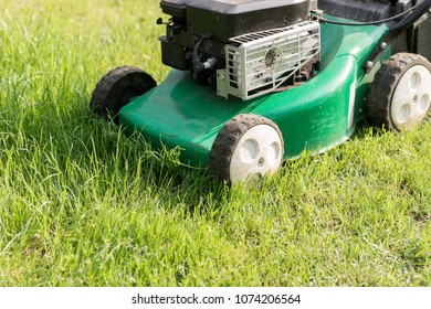 Lawn mower in the garden at work in tall grass