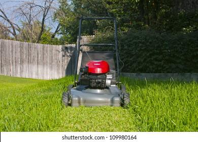 Lawn mower on cut grass path in yard