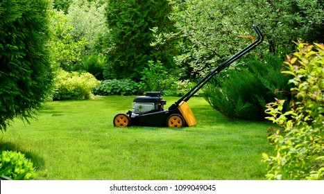 Lawn mower on the lawn on a sunny summer day in a beautiful garden.