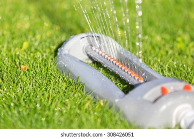 Lawn sprinkler spaying water over green grass. Irrigation system.