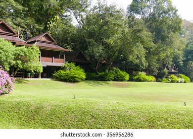 lawn yard in front of wooden traditional house in Thailand