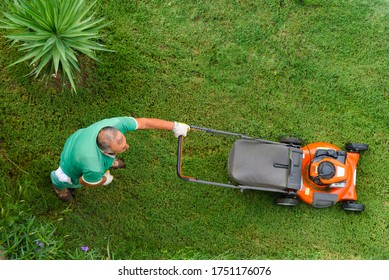 Lawnmover worker cutting green grass garden care above view