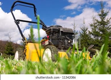 Lawnmower standing on green grass