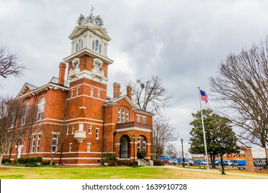 Lawrencevile,GA / USA - February 7 2020:  Front/side view of Gwinnett Historical Courthouse, showing clock tower, with flag pole and front sign