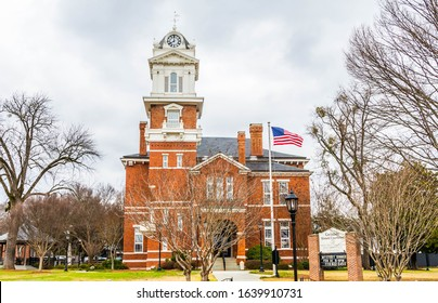 Lawrencevile,GA / USA - February 7 2020:  Front view of Gwinnett Historical Courthouse, showing clock tower, flag pole and main entrance, partially obscured by a tree, with front sign visible.