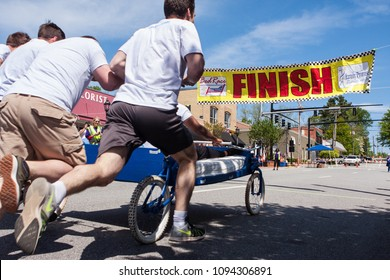 Lawrenceville, GA / USA - April 21, 2018:  A team pushes a bed on wheels toward the finish line of a charity fundraiser event on April 21, 2018 in Lawrenceville, GA.