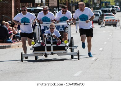 Lawrenceville, GA / USA - April 21, 2018:  A team pushes a bed down a city street in a bed race charity fundraiser event on April 21, 2018 in Lawrenceville, GA.