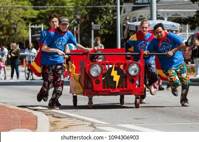 Lawrenceville, GA / USA - April 21, 2018:  A team wearing capes pushes a bed on wheels down a city street in a charity fundraiser event on April 21, 2018 in Lawrenceville, GA.