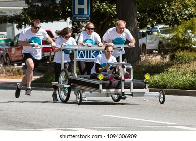 Lawrenceville, GA / USA - April 21, 2018:  A team pushes a specially designed bed in a charity fundraiser bed race event on April 21, 2018 in Lawrenceville, GA.