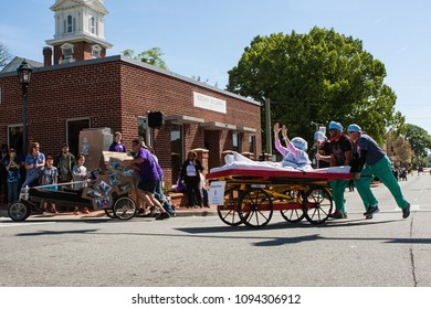 Lawrenceville, GA/ USA - April 21, 2018:  Two teams push beds on wheels around a street corner in a bed race fundraiser event on April 21, 2018 in Lawrenceville, GA.