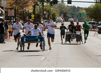 Lawrenceville, GA / USA - April 21, 2018:  A team pushes a bed on wheels in a bed race fundraiser event on April 21, 2018 in Lawrenceville, GA.