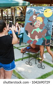 Lawrenceville, GA / USA - August 19, 2017:  A woman and pet dog pose for a photo in a cartoonish cutout of Shaggy and Scoobydoo, at Downtown Dog Day on August 19, 2017 in Lawrenceville, GA.