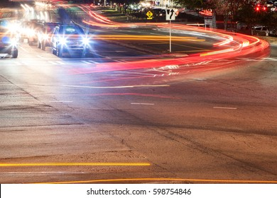 LAWRENCEVILLE, GA, USA - NOVEMBER 23, 2016:  The headlights and brakelights from cars turning at a busy intersection motion blur and streak on November 23, 2016 in Lawrenceville, GA.