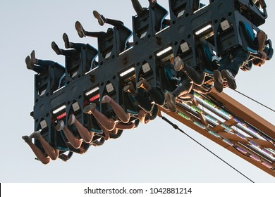Lawrenceville, GA / USA - September 22, 2017:  The legs and feet of teenagers dangle in midair on a scary ride at the Gwinnett County Fair on September 22, 2017 in Lawrenceville, GA.