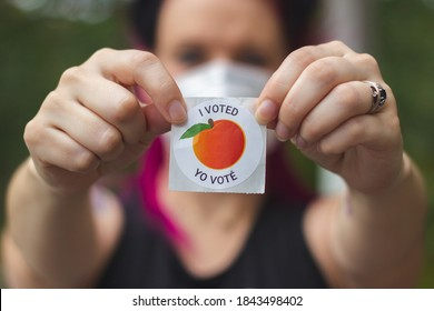 """Lawrenceville, Georgia / United States - October 29 2020: A Georgia voter wearing a mask holds up her """"I Voted"""" sticker after voting in the 2020 United States Presidential election"""