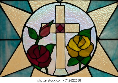 LAWRENCEVILLE, NJ - October 25, 2017: Stained glass window with a cross, red rose and yellow rose