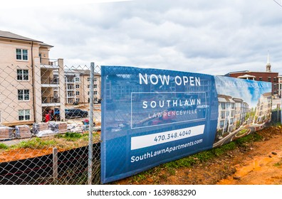 """Lawrenceville,GA / USA - February 7 2020: """"Now Open"""" Perimeter banner announcing Southlawn Lawrenceville apartments under construction along Jackson Street in Lawrenceville, Gwinnett County GA"""