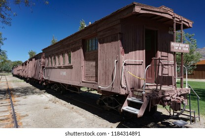 Laws, California USA: September 14, 2018: Historic narrow gauge railroad train sits on rails in Laws, California. Foreground, 1883 wooden caboose originally built as combination passenger and baggage