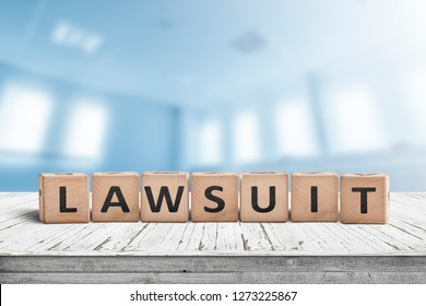 Lawsuit sign on a wooden table in a blurry bright blue room