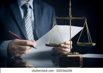 Lawyer or attorney works in his office. Scales on the desk