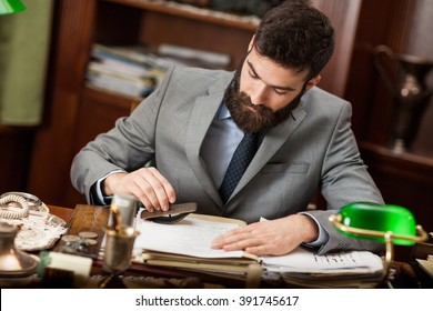 Lawyer  with a beard sitting at the table and working with important documents