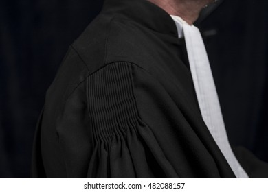 Lawyer in black gown with white jabot hands close up judge