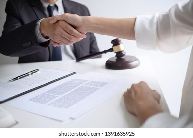 lawyer with client hands shaking in courtroom, legal and justice concept.