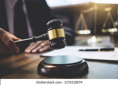 Lawyer or counselor working on a documents and holding gavel in Courtroom, Justice and Law concept.