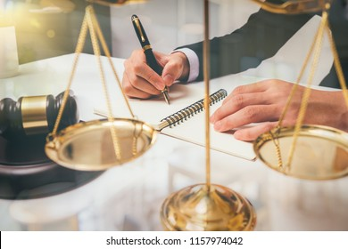 lawyer Detail of a judge sitting at his desk, studying new laws and legislation and taking notes. Selective focus,warm colours sun light