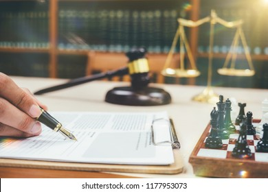 lawyer Detail of a judge sitting at his desk, studying new laws and legislation and taking notes. Selective focus