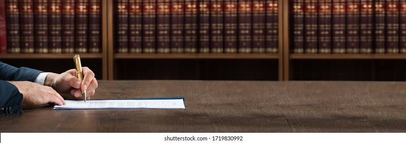 Lawyer Doing Legal Document Scrutiny At Desk With Books At Background