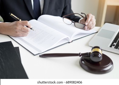 lawyer hand writes the document in court (justice, law) with sounding block.
