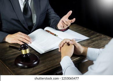 Lawyer or judge consult meeting with client at a law firm about legal legislation in courtroom with Judge gavel and Gold brass balance scale